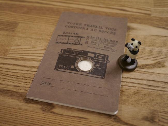 カメラのイラストが描いてあるちょっとレトロな雰囲気のノートです。